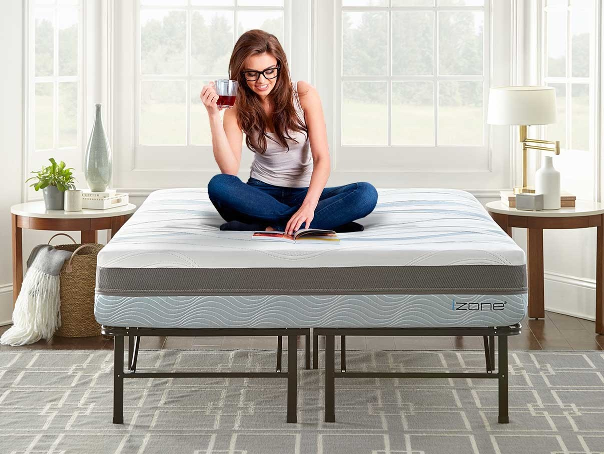 Young woman sitting on the izone bed with platform bed frame mattress set