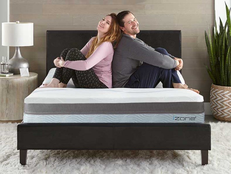 Happy couple sitting back to back on the izone bed in bedroom setting