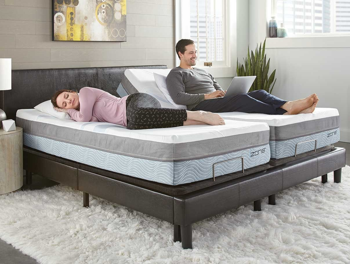 Happy couple sleeping and working in their izone adjsutable bed set